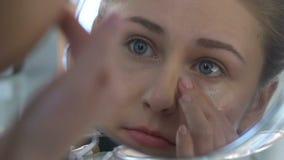 Mujer joven que aplica la crema del ojo, cosmético de la anti-edad, cuidado de piel, rejuvenecimiento