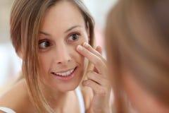 Mujer joven que aplica la crema en cara Fotografía de archivo libre de regalías