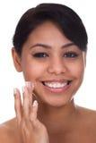 Mujer joven que aplica la crema en su cara imagen de archivo