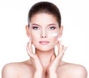 Mujer joven que aplica la crema en su cara bonita Fotografía de archivo libre de regalías