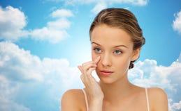 Mujer joven que aplica la crema a la cara sobre el cielo azul Fotografía de archivo libre de regalías