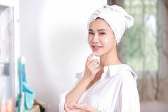 Mujer joven que aplica la crema a la reflexión de espejo de la cara en el vestido imagen de archivo libre de regalías