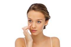 Mujer joven que aplica la crema a su cara Imagenes de archivo