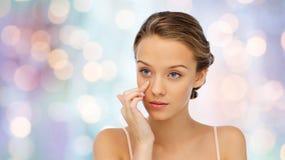 Mujer joven que aplica la crema a su cara Fotografía de archivo