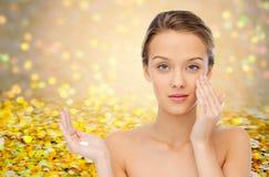 Mujer joven que aplica la crema a su cara Imagen de archivo libre de regalías