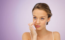Mujer joven que aplica la crema a su cara Imagen de archivo
