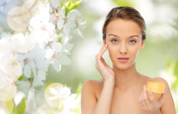 Mujer joven que aplica la crema a su cara Imágenes de archivo libres de regalías