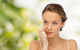Mujer joven que aplica la crema a su cara Fotos de archivo libres de regalías