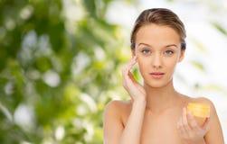 Mujer joven que aplica la crema a su cara Foto de archivo libre de regalías