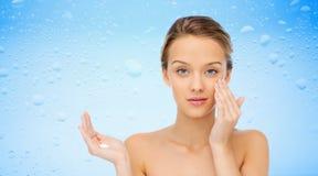 Mujer joven que aplica la crema a su cara Fotografía de archivo libre de regalías