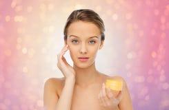 Mujer joven que aplica la crema a su cara Fotos de archivo