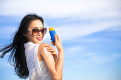 Mujer joven que aplica la loción de la protección del sol Fotografía de archivo