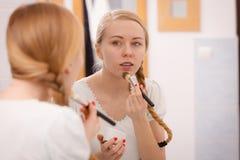 Mujer joven que aplica la máscara del fango en cara Fotos de archivo libres de regalías