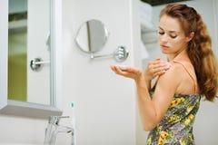 Mujer joven que aplica la nata de la carrocería en hombro Imagen de archivo libre de regalías