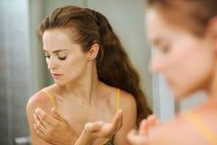 Mujer joven que aplica la nata en hombro en cuarto de baño Foto de archivo libre de regalías