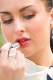 Mujer joven que aplica los cosméticos en sus labios Foto de archivo libre de regalías