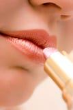 Mujer joven que aplica los cosméticos en sus labios Fotos de archivo