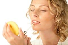 Mujer joven que aplica lustre del labio Fotos de archivo libres de regalías