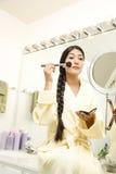 Mujer joven que aplica maquillaje imágenes de archivo libres de regalías