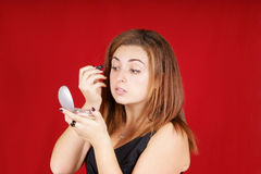 Mujer joven que aplica maquillaje Fotos de archivo libres de regalías