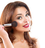 Mujer joven que aplica maquillaje foto de archivo