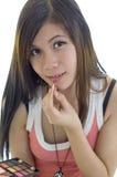 Mujer joven que aplica maquillaje Fotografía de archivo libre de regalías