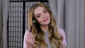 Mujer joven que aplica maquillaje con un cepillo delante de un espejo metrajes