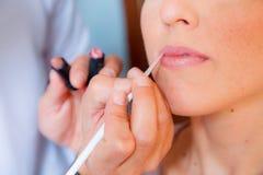 Maquillaje. aplicación del lápiz de los labios foto de archivo