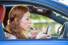 Mujer joven que aplica maquillaje mientras que conduce el coche Imagen de archivo