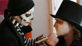 Mujer joven que aplica maquillaje sobre cara del ` s del hombre en Halloween metrajes