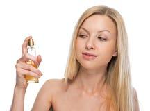Mujer joven que aplica perfume Imagenes de archivo