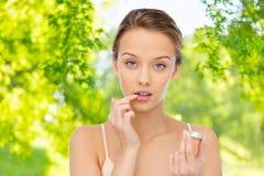 Mujer joven que aplica protector labial a sus labios Imagen de archivo libre de regalías