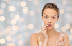 Mujer joven que aplica protector labial a sus labios Fotografía de archivo