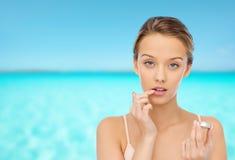Mujer joven que aplica protector labial a sus labios Imagenes de archivo