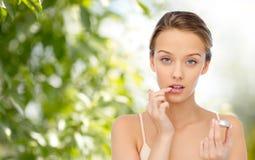 Mujer joven que aplica protector labial a sus labios Fotos de archivo
