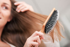Mujer joven que aplica su pelo con brocha Imágenes de archivo libres de regalías