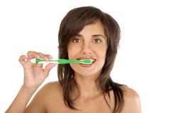 Mujer joven que aplica sus dientes con brocha Imagen de archivo libre de regalías