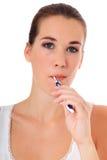 Mujer joven que aplica sus dientes con brocha Fotografía de archivo