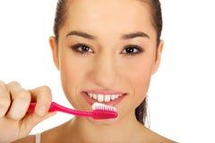Mujer joven que aplica sus dientes con brocha Fotos de archivo