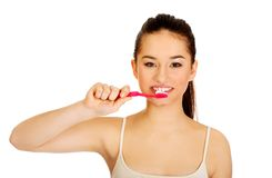 Mujer joven que aplica sus dientes con brocha Imagen de archivo
