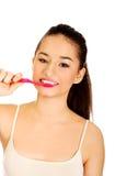 Mujer joven que aplica sus dientes con brocha Fotos de archivo libres de regalías