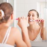 Mujer joven que aplica sus dientes con brocha delante de un mirro Imagenes de archivo