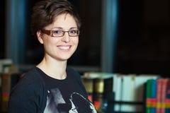Mujer joven que aprende en biblioteca Imágenes de archivo libres de regalías