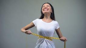 Mujer joven que aprieta a la cinta métrica, torturándose con dieta, bulimia almacen de metraje de vídeo