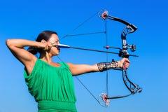 Mujer joven que apunta la flecha del arco compuesto foto de archivo libre de regalías