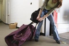 Mujer joven que arrastra un bolso Fotografía de archivo libre de regalías