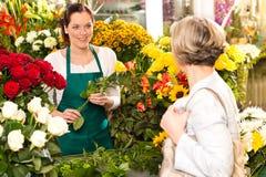 Mujer joven que arregla la venta del mercado del departamento de flores Imagenes de archivo