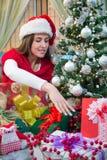 Mujer joven que arregla regalos de Navidad debajo del árbol Imagenes de archivo
