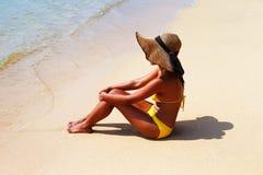Mujer joven que asienta abajo en un baño de la playa arenosa y de sol Foto de archivo libre de regalías