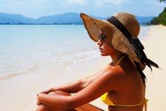 Mujer joven que asienta abajo en un baño de la playa arenosa y de sol Imagen de archivo
